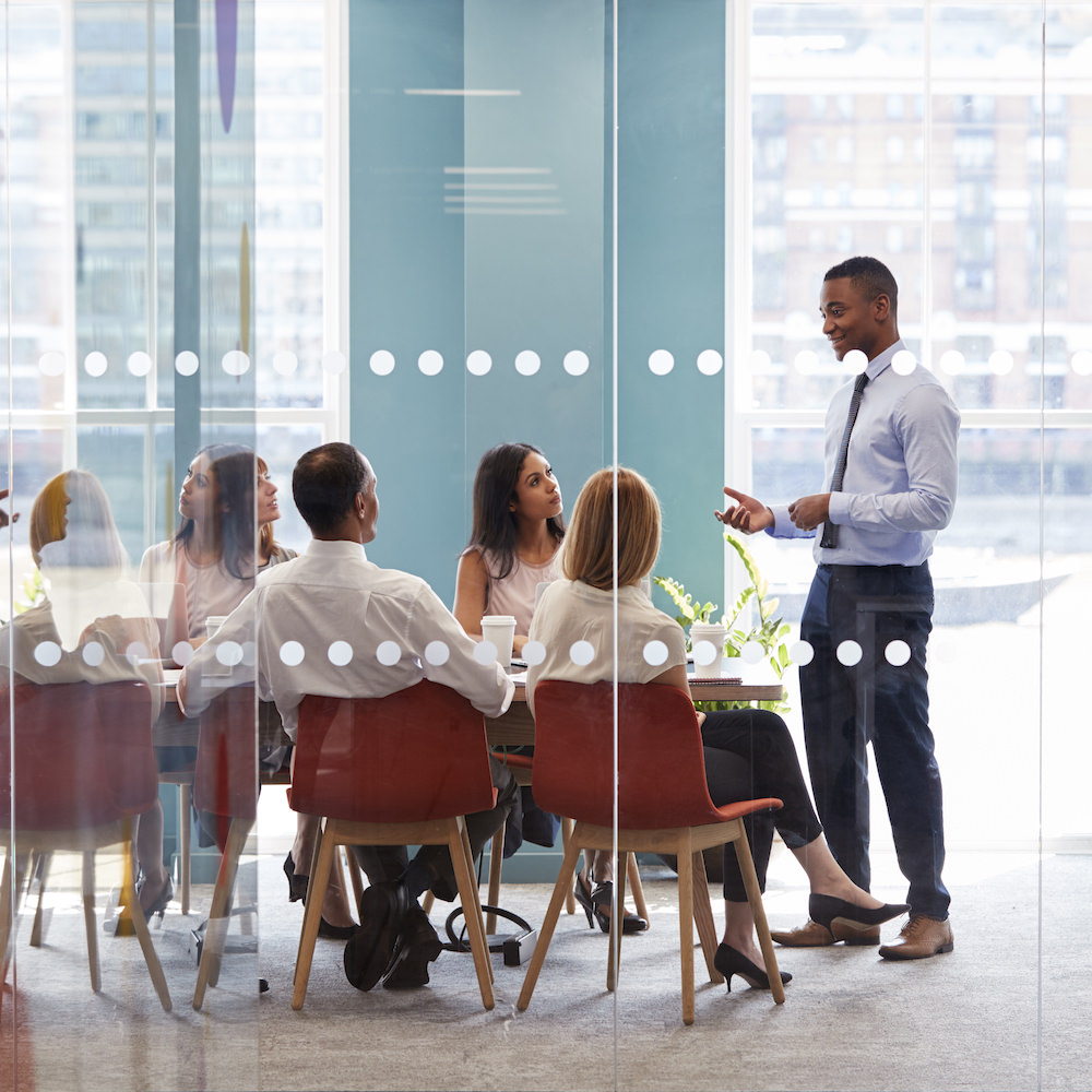 Young male boss stands addressing business team at meeting